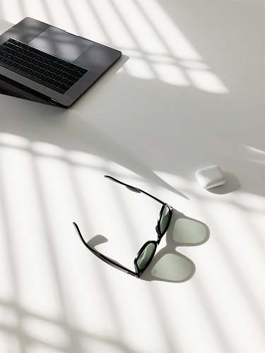sunglass flat-lay photography of wayfarer-style sunglasses and MacBook Pro glasses