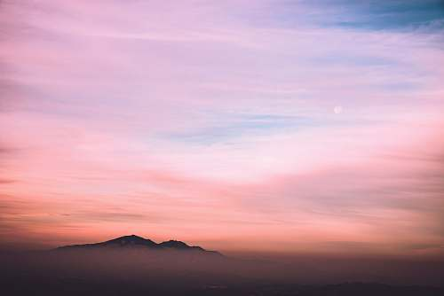 sunset black mountain under blue and white sky nature