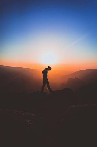 sunset silhouette of man standing on mountain peak silhouette