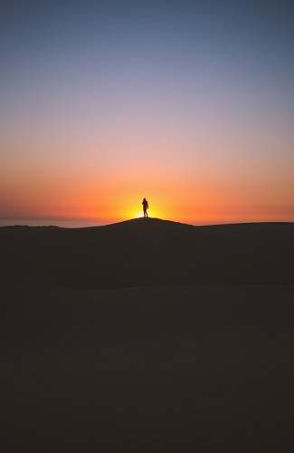 sunset silhouette of person standing on hill sky