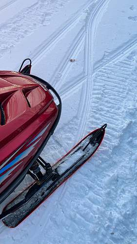 vehicle red and black snow sled on snow covered ground during daytime boat