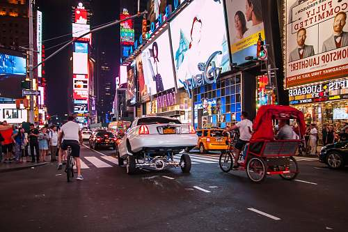 times square vehicle on road at night-time new york