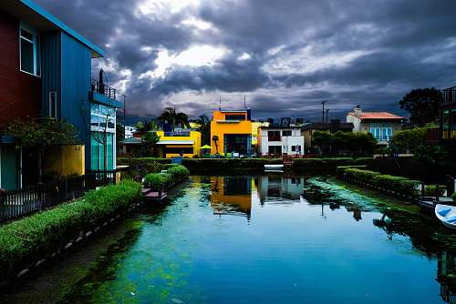 nature buildings near body of water under cloudy sky during daytime outdoors