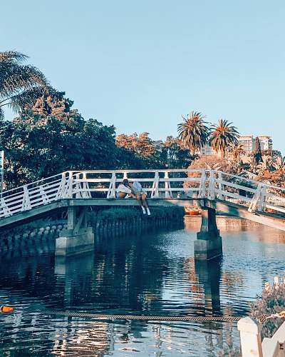 bridge couple kissing on top of gray and white metal bridge venice canals