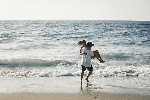 people man carrying woman on seashore beach