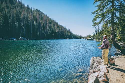 lake man standing on rock on front of lake surrounded with trees at daytime fishing