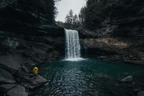grey person in front of waterfalls waterfall