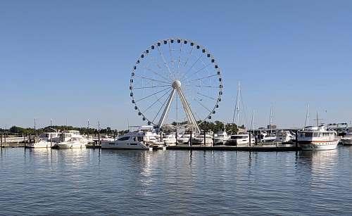 waterfront white ferris wheel near body of water during daytime boat
