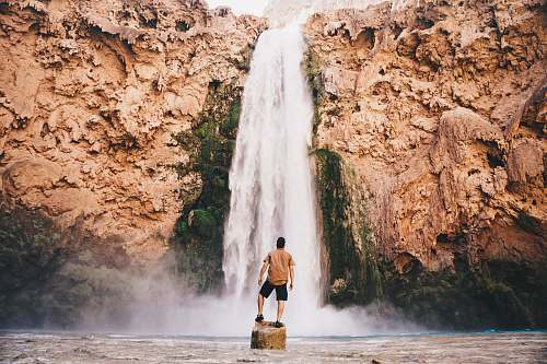 outdoors man standing on stone in front of waterfall havasupai reservation