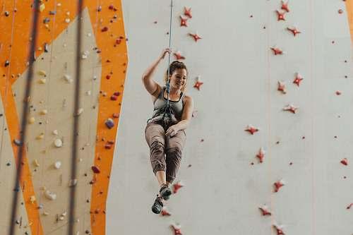 climbing woman holding gray harness near multicolored wal sport