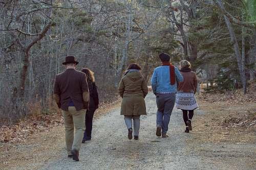 clothing five people walking between trees shoe