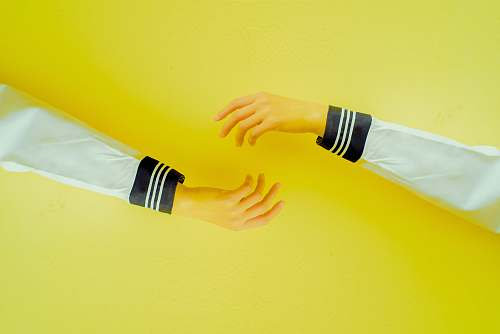 clothing two hands reaching each other on yellow background arm