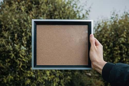 frame person holding rectangular white and black frame blank frame
