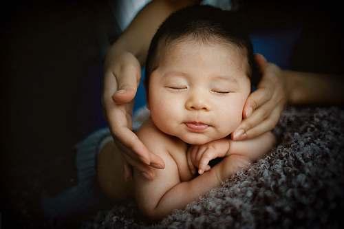 people baby lying on gray textile kid