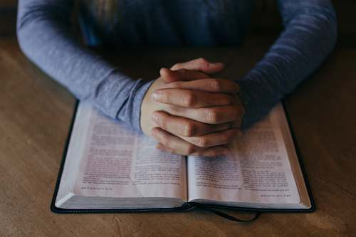 prayer man holding his hands on open book faith