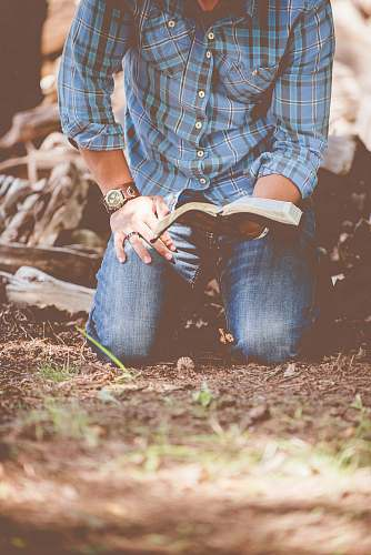 prayer person reading book while kneeling christian