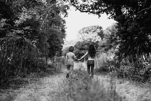 holding hands grayscale photo of boy and girl walking on path hand