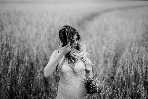 person grayscale photo of woman surrounded by grass wheat