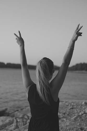 child grayscale photo of woman wearing black tank top walking on seashore while doing peace hand sign teen