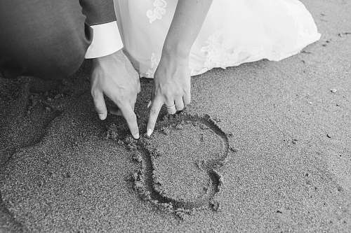 grey grayscale photography of man and woman draw heart on sand wedding