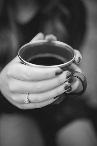 cup grayscale photography of person holding mug coffee cup
