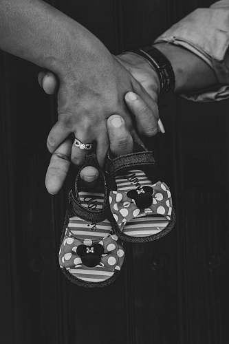 apparel grayscale photography of two person holding hands holding toddler shoes clothing