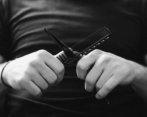 hand grayscale photography person holding scissors and hair comb finger