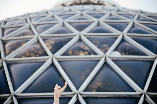 architecture closeup photo of person pointing glass roof dome