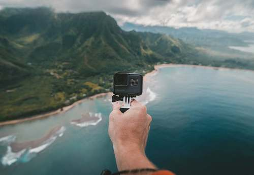 island person holding black action camera fronting green mountains ocean