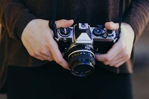 human person holding gray and black SSLR camera person
