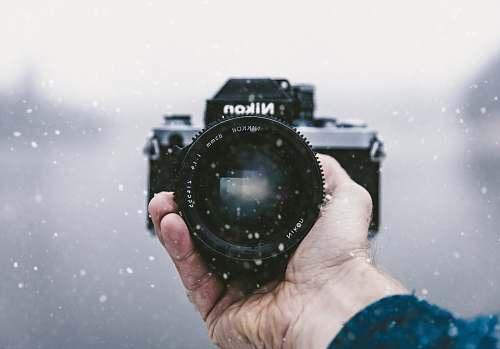 nikon person holding Nikon DSLR camera snowfall