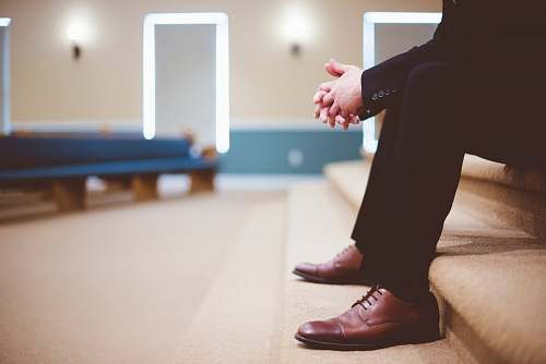 man man in black pants and pair of brown leather lace-up shoes sitting on brown carpeted stairs inside room sitting