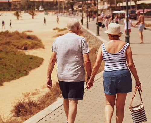 apparel man and woman walking on road while holding hands shorts