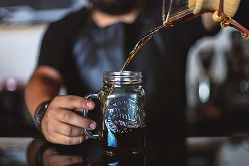jar man pouring liquid on clear glass mason jar glass