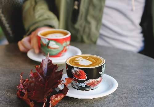drink selective focus photo of black floral cup on white saucer with latte fall