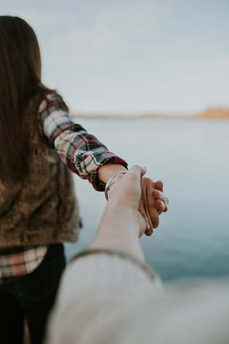 people shallow focus photography of man and woman holding hands woman