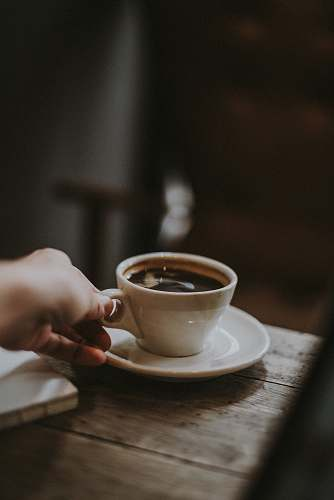 coffee person holding white ceramic cup with liquid coffee cup