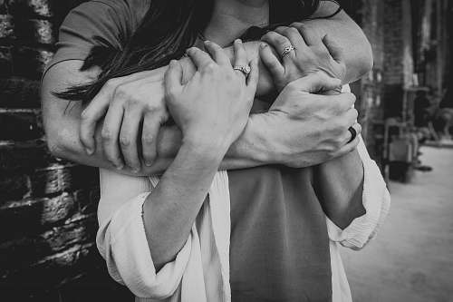 black-and-white grayscale photo of man hugging woman grey