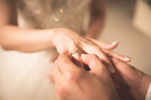 human man holding gold ring on woman's finger person