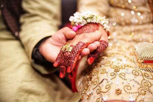 hand person holding hands wearing gold-colored ring henna