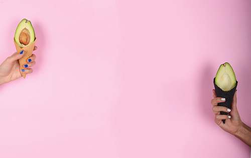 pink person holding avocado background