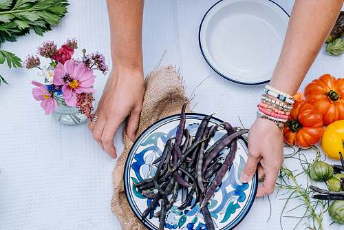 arm person holding white and blue floral ceramic plate with string beans atop near heirloom tomatoes hand