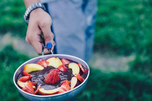hand person holding pan filled with sliced strawberries pan