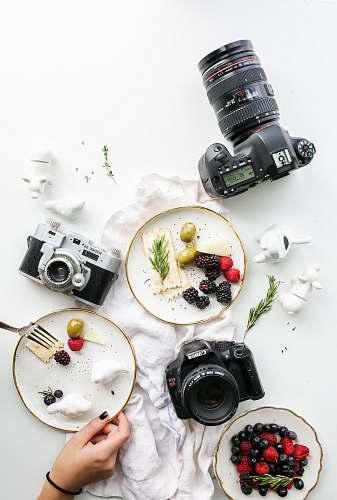 camera three assorted cameras near fruits and ceramic figurines food