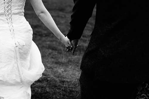 black-and-white bride and groom holding hands together holding hands