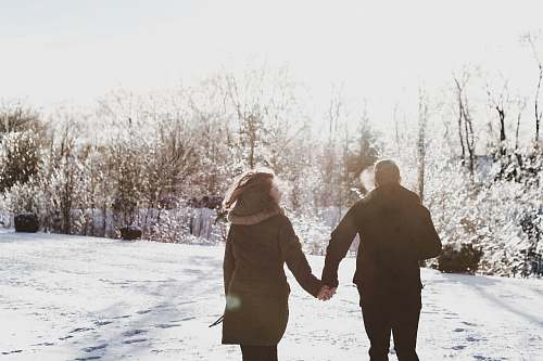 holding hands couple holding hand while walking on snow covered field human