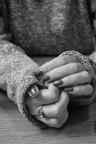 finger grayscale photo of person in long-sleeved top and manicure black-and-white