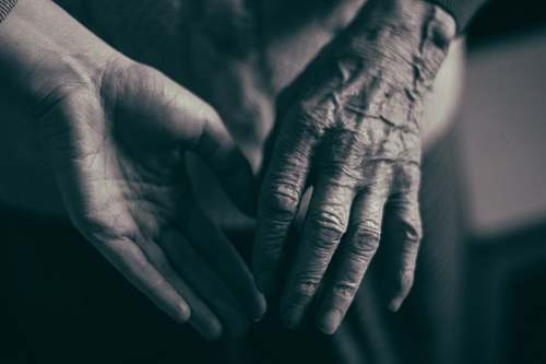 grey grayscale photo of two hands about to hold finger