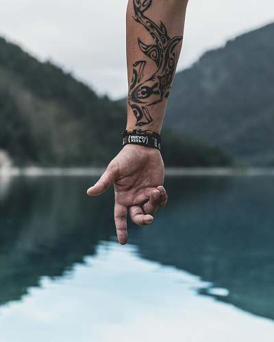 tattoo hand of person pointing to body of water with wrist tattoo holding hands