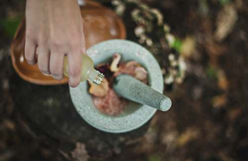 healing high angle photo of person pouring liquid from bottle inside mortar and pestle mortar